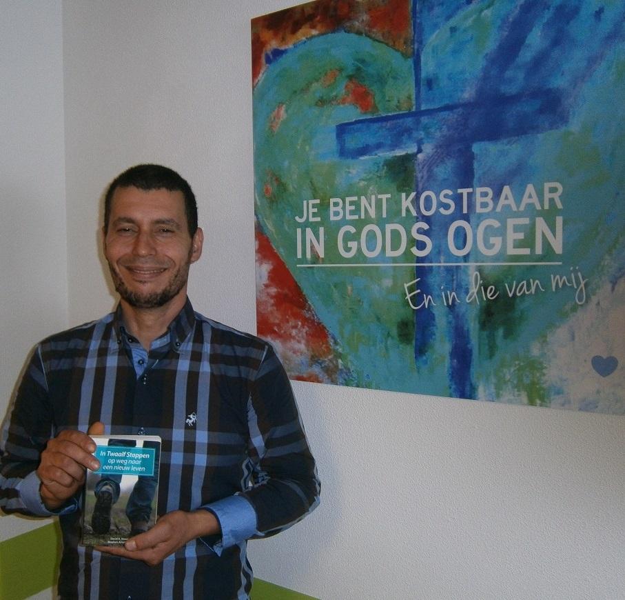 Hier staat hij bij het bemoedigende schilderij in het inloophuis van Sta Op Zorg, met het boek: In Twaalf Stappen op weg naar een nieuw leven